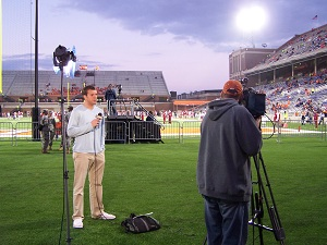 sports reporter adam mikulich at football game
